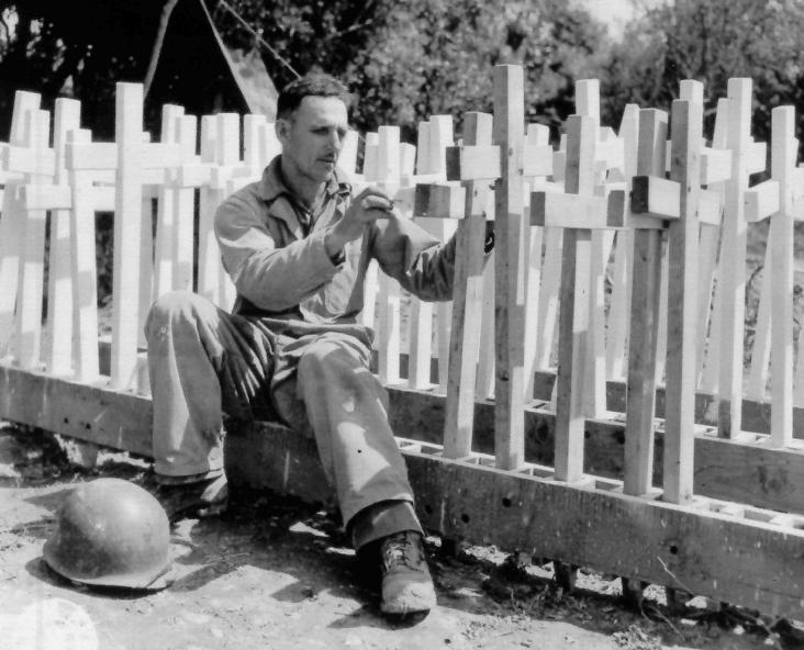 2 Graves Registration soldier checks temporary crosses before use in the field