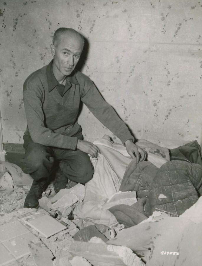 Ernie Pyle looking at his bed, from which he had just left to watch the bombing, when the roof fell on it.