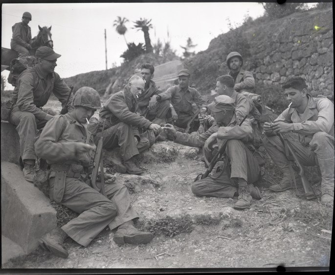 Ernie Pyle rests on the roadside with a Marine patrol, April 8, 1945. Photo courtesy of National Archives