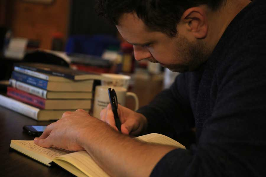 Adam Linehan works on a writing piece during a War Horse writing seminar for medics. Photo courtesy of Evy Mages.