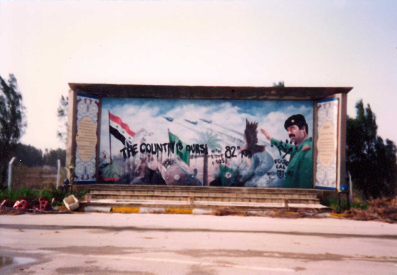 """""""The Country Is Ours,"""" signed """"82nd."""" The work of two soldiers serving in the 82nd Airborne, the defaced mural of Saddam Hussein was located near the front gate of Tallil Air Base. Photo courtesy of Harry L. Whitlock."""